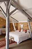 Rustic attic bedroom with exposed wooden roof structure, stone walls and Moroccan rug next to bed