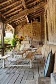 Vase of sunflowers on combined table and benches on rustic veranda with wooden floor