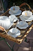 White china tea service in leaf design on wicker tray on metal stand