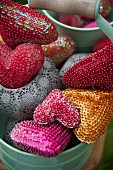 Collection of small, sequinned cushions in metal container