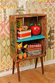 Retro-style child's bedroom with DIY shelves made from old wooden crate and 50s cabinet legs; old tin, vintage Bert and Happy Apple toys against patchwork of 70s wallpaper