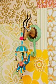 Retro ornaments in child's bedroom; Indian elephant mobile hanging from tin coat hook shaped like hunting trophy on patchwork of 70's wallpapers