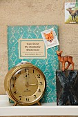 Vintage ornaments on bookshelf; animal-motif postage stamps, decorative book cover, toy deer, X and 8 printing blocks and 60s Junghans alarm clock