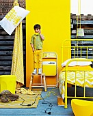 Yellow furnishings for a child's bedroom in front of yellow panel; small boy wearing yellow trousers standing on stool