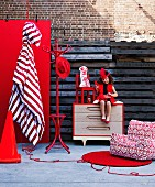 Bright red home accessories and furniture with little girl in red dress sitting on chest of drawers