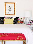 Double bed with white throw and several decorative pillows in different patterns; at the foot end a red upholstered stool with a floral motif
