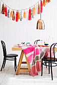 Cheerful tablecloth on dining table below copper pendant lamp and garland of shiny paper tassels