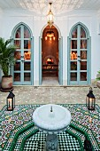 View from Oriental, tiled courtyard with fountain through terrace doors into festive candlelit interior with inviting open fire