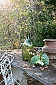 Autumnal still-life of broccoli, jars and urn on stone table in garden