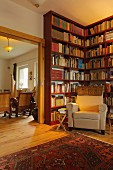 Library in village house with floor-to-ceiling bookcases and armchair (Eggelingen, East Frisia, Germany)
