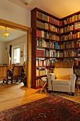 Bibliothek mit deckenhohen Bücherregalen und Sessel in Dorfhaus (Eggelingen, Ostfriesland)