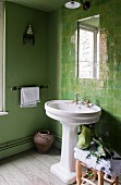 Green bathroom with pedestal sink & tiled wall