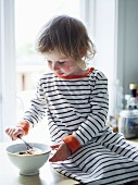 A girl eating breakfast on a worktop, Sweden.