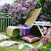 Wickerwork lounger in front of flowering lilac bush