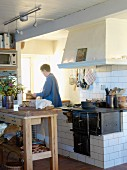 Woman in old, Swedish kitchen with large chimney breast over masonry range