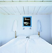 Simple, rustic bedroom with shirts hanging on wooden bedposts either side of niche with blue frame