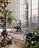 Wrought iron lounger and conservatory furnishings with trailing ivy combined with floral wallpaper and carpet