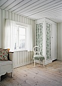 Pale room in Scandinavian wooden house with wide stripes on walls and fitted wardrobe with floral, fabric door panels