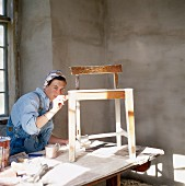 Woman in overalls painting wooden chair on table covered with newspaper