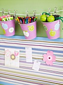 Pens in metal beakers with printed patterns pegged on cord above striped pinboard with pictures of flowers