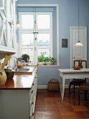 Traditional Scandinavian-style kitchen-dining room painted sky blue with old, glass pendant lamps