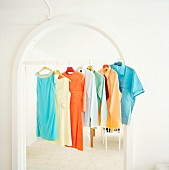 Colourful shirts and dresses hanging on frame of arched doorway
