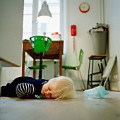 Toddler asleep on kitchen floor with dropped-out dummy; bright green suspended highchair at dining table in background