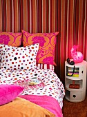 Coffee cup on tray and telephone on side table in bedroom; mixture of red and pink patterns on wall and bed linen