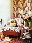 Upholstered armchair overloaded with lace cloths and rose-patterned cushions in front of wallpaper with large floral motif
