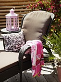 Lounger with cushion, towel and scatter cushion in front of lantern on side table