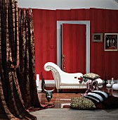 Sophisticated living room with white chaise longue and elegant cushions on floor in front of red wallpapered wall with lengths of fabric draped to one side
