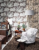 Fifties-style armchair and classic designer stool on flokati rug next to modern standard lamp against wall with patterned wallpaper