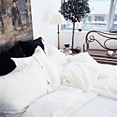 Bed with white bed linen and antique bench below window