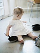 A little girl playing in a kitchen