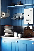 Detail of kitchen sink with stacked plates against blue-painted wooden wall