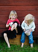 Little girls holding pots sitting and playing against outer wall of wooden cabin
