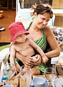 Mother sitting on veranda with toddler on lap