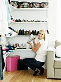 Teenage girl showing collection of shoes