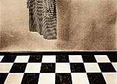Coat hanging above chequered floor