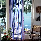 Stuhl mit Geflecht neben Terrassenglastür und Blick auf an Haus anschliessendem Holzsteg am See