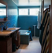 Bathroom with washstand and fitted bathtub against wall with blue mosaic tiles and transom windows