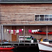 Wooden house with laundry hanging to dry and moored boats on lake shore