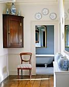 Verschiedenes Blauweiss-Geschirr in einem Vorraum mit Blick ins Bad auf Wanne und Antikspiegel
