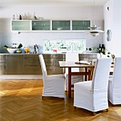 Einbauküche mit Edelstahlfronten und Essplatz mit Hussenstühlen