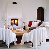 Decken und Kissen auf Sitzmöbeln vor gemauertem Kaminofen und rustikaler Rundbogentür