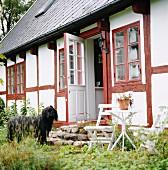 Hund vor altem, ländlichem Fachwerkhaus mit rot gestrichenen Fensterrahmen und Holzbalken