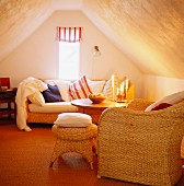 Cosy attic room with basketwork seating and striped Roman blind on narrow gable window