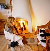 Frau vor offenem Kaminfeuer und Katze auf Korbstuhl