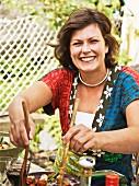 Woman serving salad, smiling, portrait