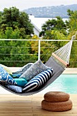 Patterned cushions on comfortable, blue canvas hammock above two woven seagrass pouffes